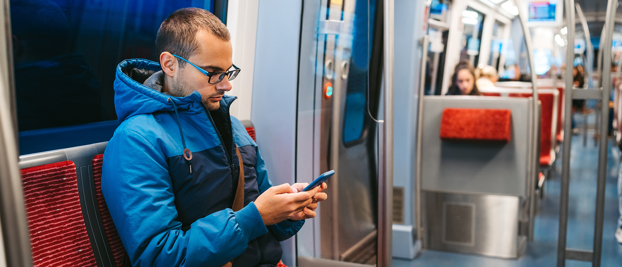Young man riding the subway is using phone for an online doctor visit