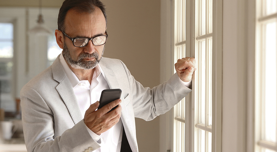 A Hispanic businessman in his mid fifties, wearing a light gray suit and a pair of eyeglasses, looks at his mobile phone as he leans against a row of windows as he works from home.