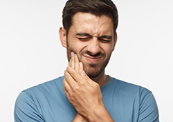Young male with his face distorted in pain, hands pressed to cheek as he is experiencing severe toothache or tooth pain