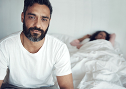 Man with erectile dysfunction (ED) sitting on bed with wife in background