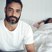 Portrait of a mature man looking upset while his wife sleeps in the background