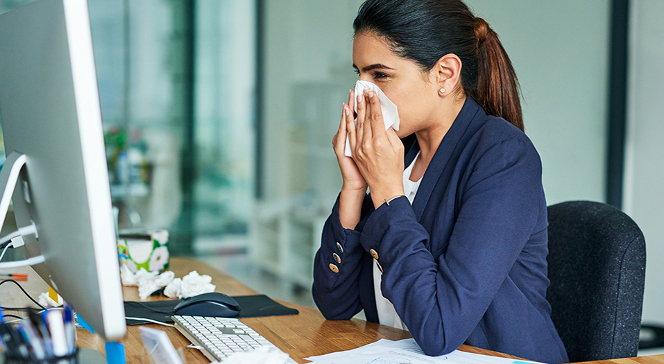 Shot of a young businesswoman blowing her nose while working in an office