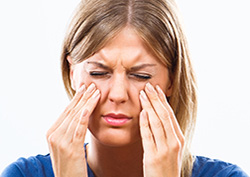 Woman with a sinus infection is holding her cheeks with both hands, appearing to be in pain