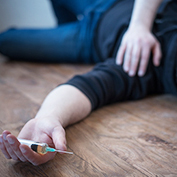 Man lying down on the floor after a drug overdose. He can be treated with Naxolone nasal spray