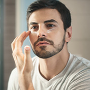Metrosexual man applying lotion for anti-aging treatment around eye