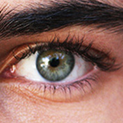 Green eye of a young man with long eyelashes after using latisse